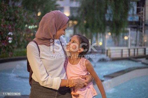 A beautiful muslim mother holds her daughter in her arms. They are both looking at each other.