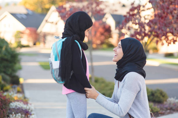 Muslim mother asks her daughter how her day at school was stock photo