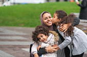 A family of Middle Eastern descent is spending time together. A young mother is playing at the park with her two young daughters. The mother is kneeling down and embracing her children. The happy group is smiling. The older daughter is giving her mom a kiss on the cheek.