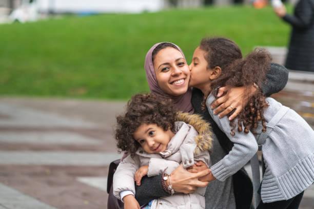 muslim mother hugging daughters in city park - скромная одежда стоковые фото и изображения