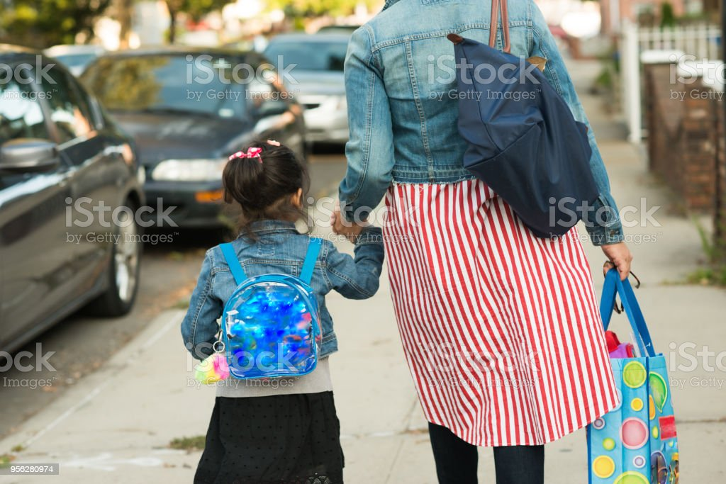 muslim mother in hijab taking daughter to school stock photo
