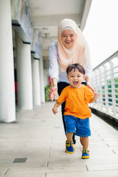 Muslim mother laughing behind running young son Muslim mother laughing behind running young son religious dress stock pictures, royalty-free photos & images