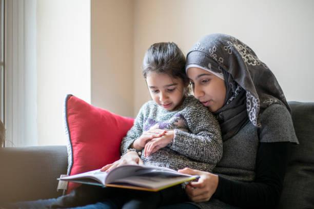 muslim mother reading to her daughter - скромная одежда стоковые фото и изображения