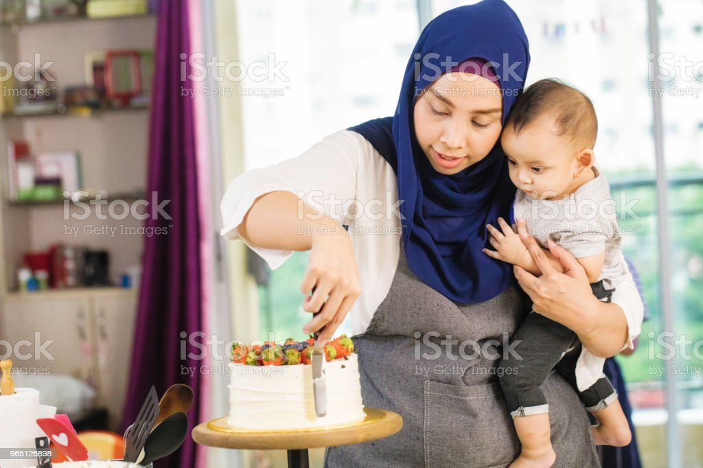 Muslim mother showing attentive baby how to ice a cake royalty-free stock photo