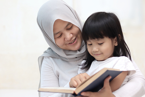 Muslim mother teach her daughter how to read the holy quran
