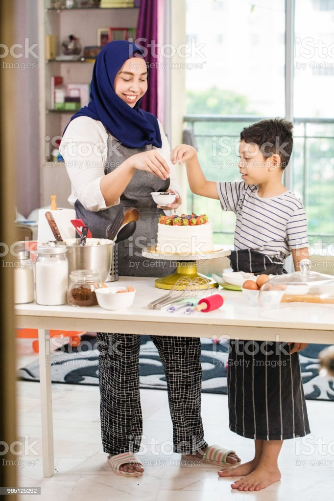 Muslim mother teaching son how to decorate cake with fresh fruit full length zbiór zdjęć royalty-free