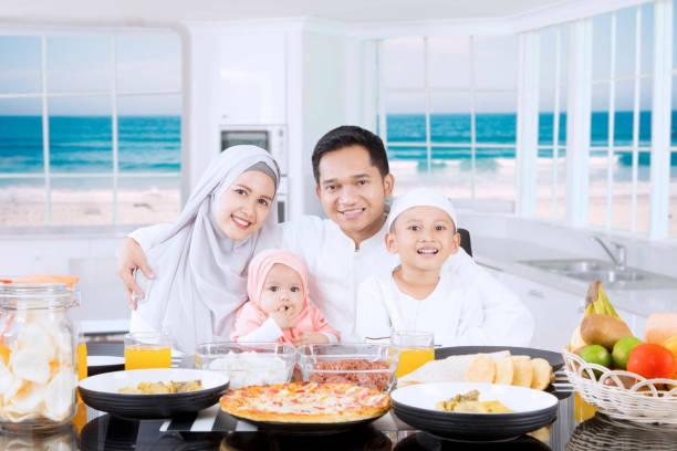 muslimische eltern und kinder lächeln - küstenfamilienzimmer stock-fotos und bilder