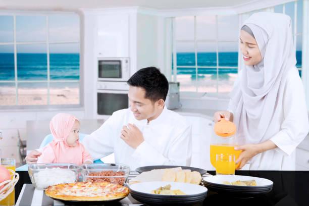 muslimische eltern und tochter lächelnd zusammen - küstenfamilienzimmer stock-fotos und bilder