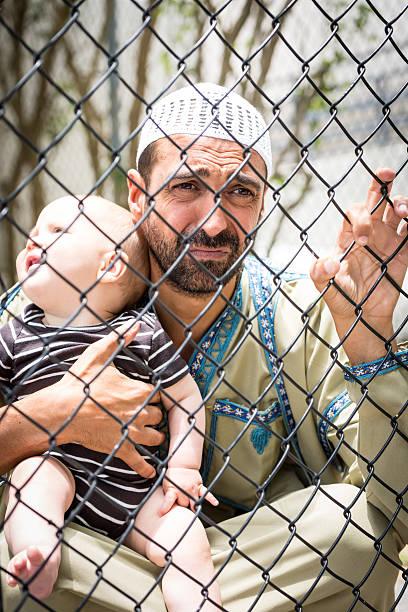 Muslim refugee holding his baby stock photo