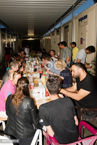 istock Muslim refugees and German volunteers sit together eating dinner during 542109516