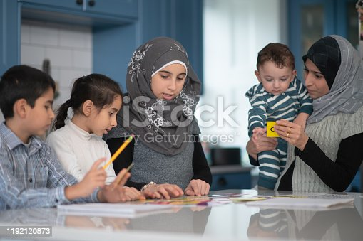 A group of Muslim siblings sit at the kitchen island working on language homework.  They are working with word cue cards and have their notebooks open with pencils in hand.  Their Mom is holding their baby brother and playing with him, as she oversees the school work.  They are all dressed casually and the eldest and Mother are wearing a hijab.