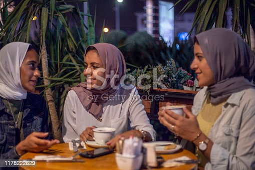Three (3) beautiful muslim sisters talk over a cup of tea at a cafe. They are all focused on the woman sitting on the far left.