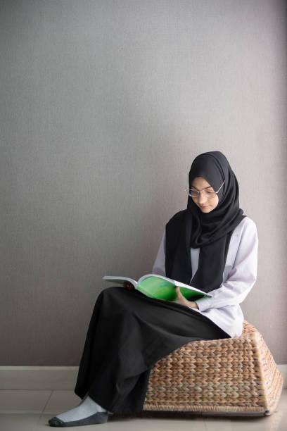 Libro de lectura de estudiantes musulmanes en la sala. - foto de stock
