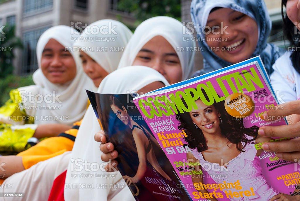 Muslim students reading Cosmopolitan magazine in Malaysia stock photo