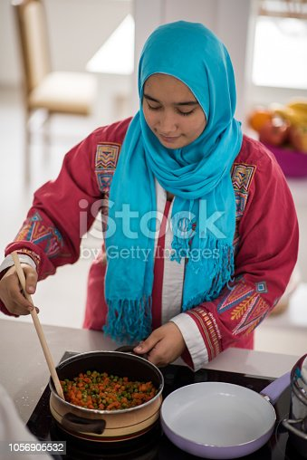 Muslim traditional young girl making food in kitchen