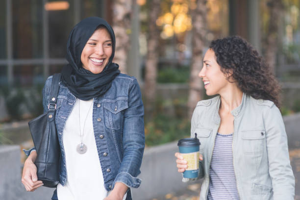 A Muslim woman and her friend walking together in the city stock photo