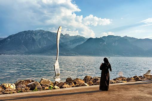 Muslim woman at Fork sculpture at Geneva Lake of Vevey