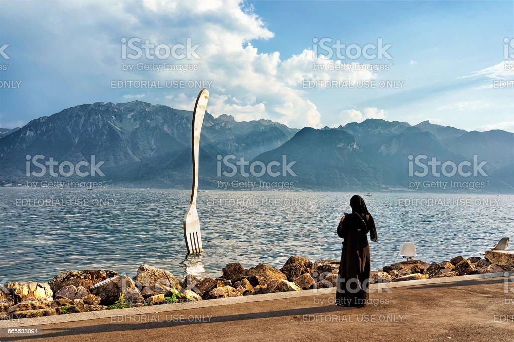 Muslim woman at Fork sculpture at Geneva Lake of Vevey stock photo