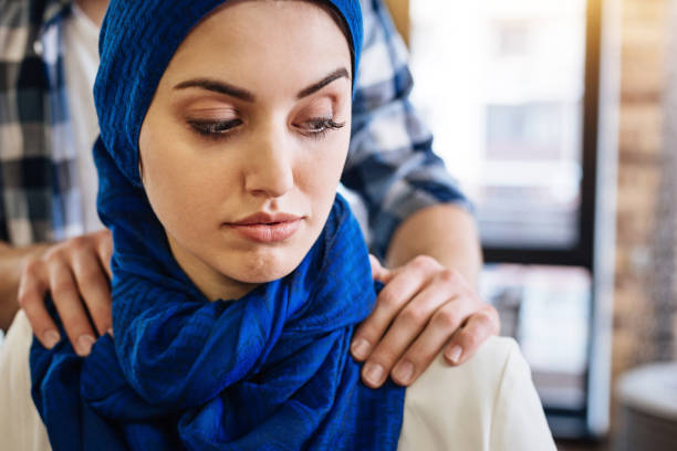 Muslim woman beign herrased by representative of another group stock photo