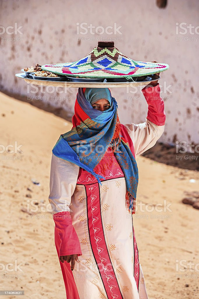Muslim woman carrying food on her head in Southern Egypt royalty-free stock photo
