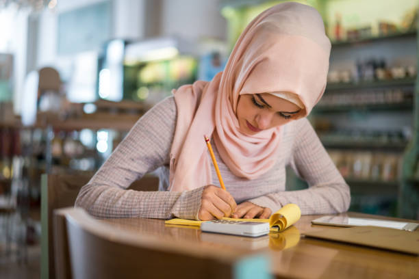 Muslim woman doing the books at a restaurant stock photo