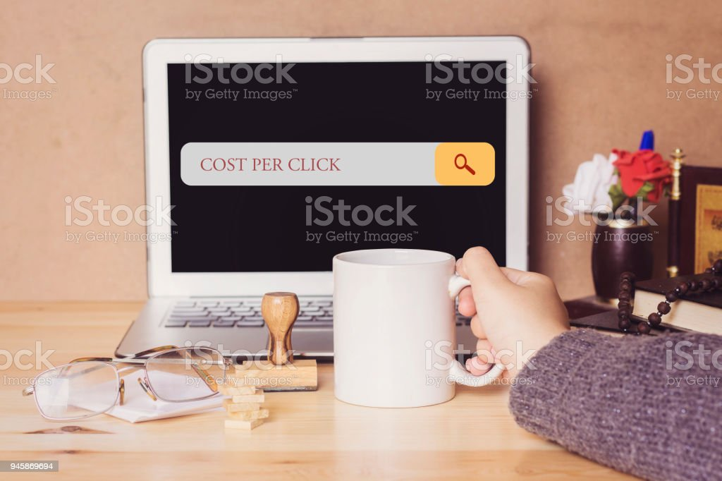 muslim woman drinking a coffee and searching cost per click in search bar – zdjęcie