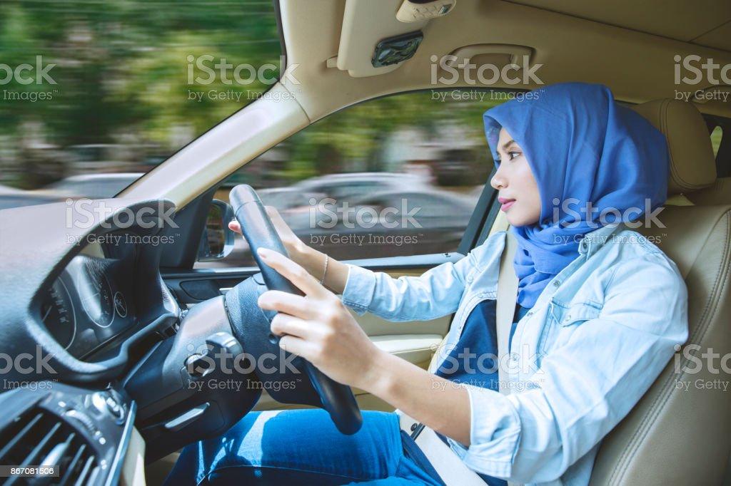 Muslim woman driving a car stock photo
