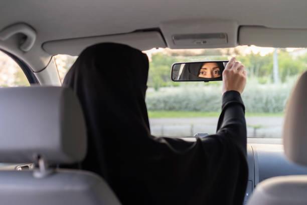 muslim woman driving a car - saudi woman stock photos and pictures