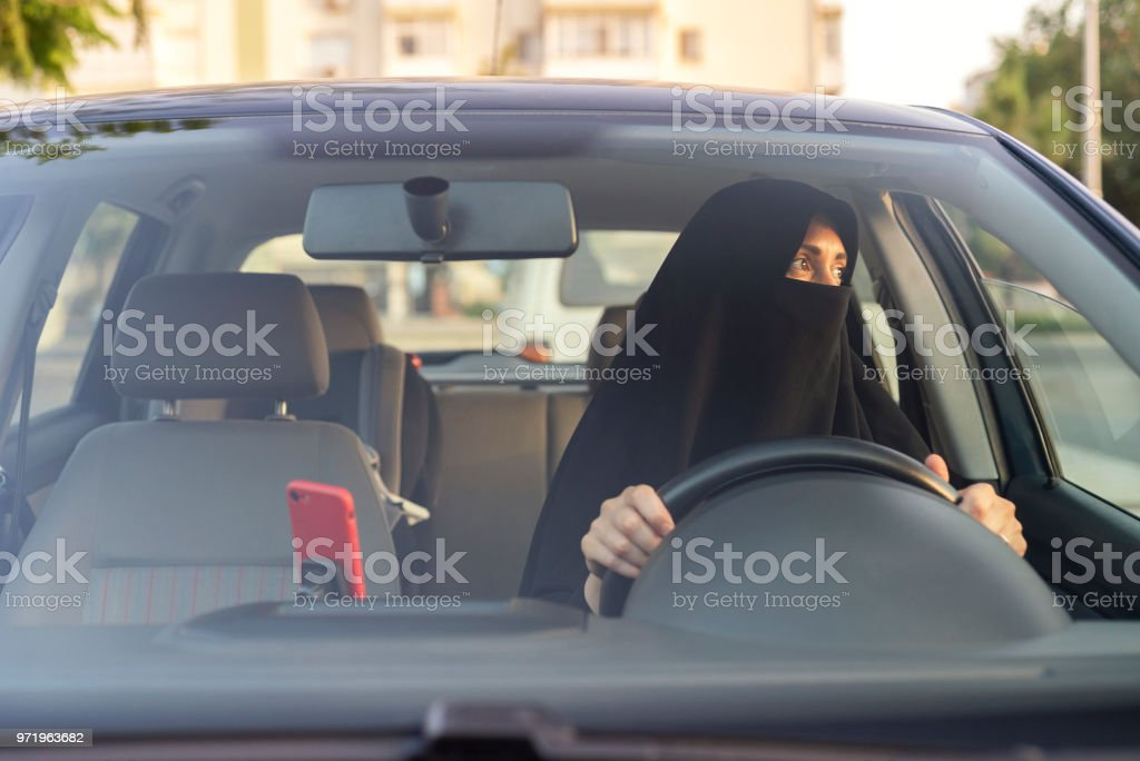 Muslim woman driving a car stock photo