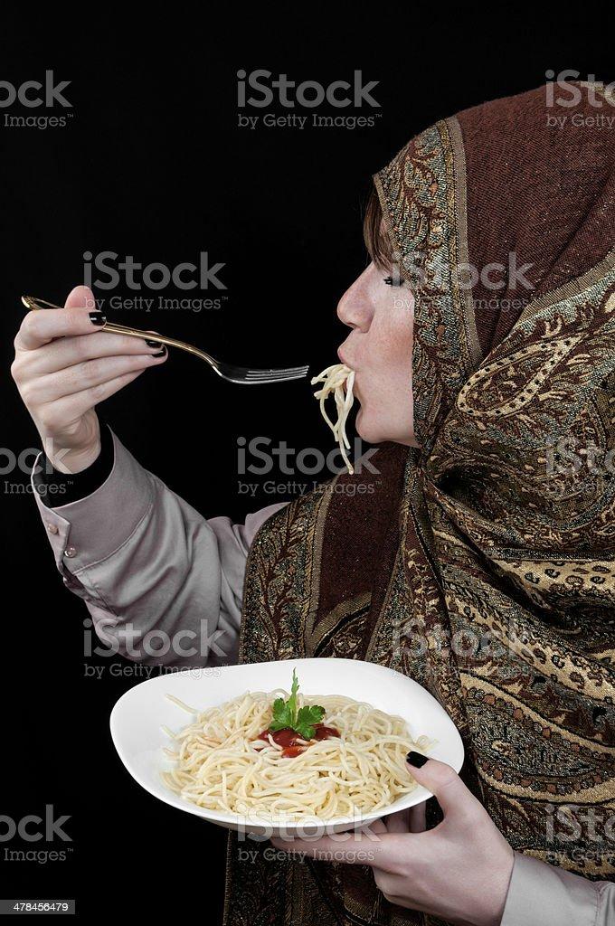 Muslim woman eating pasta royalty-free stock photo