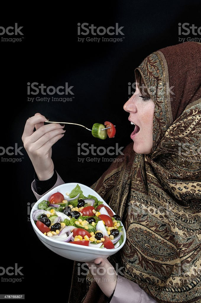 Muslim woman eating salad royalty-free stock photo