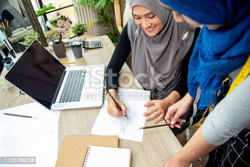 Muslim woman fashion designer team discussing dress sketch in paper at the table in tailor shop