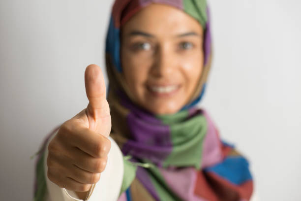 Muslim woman giving thumbs up sign stock photo