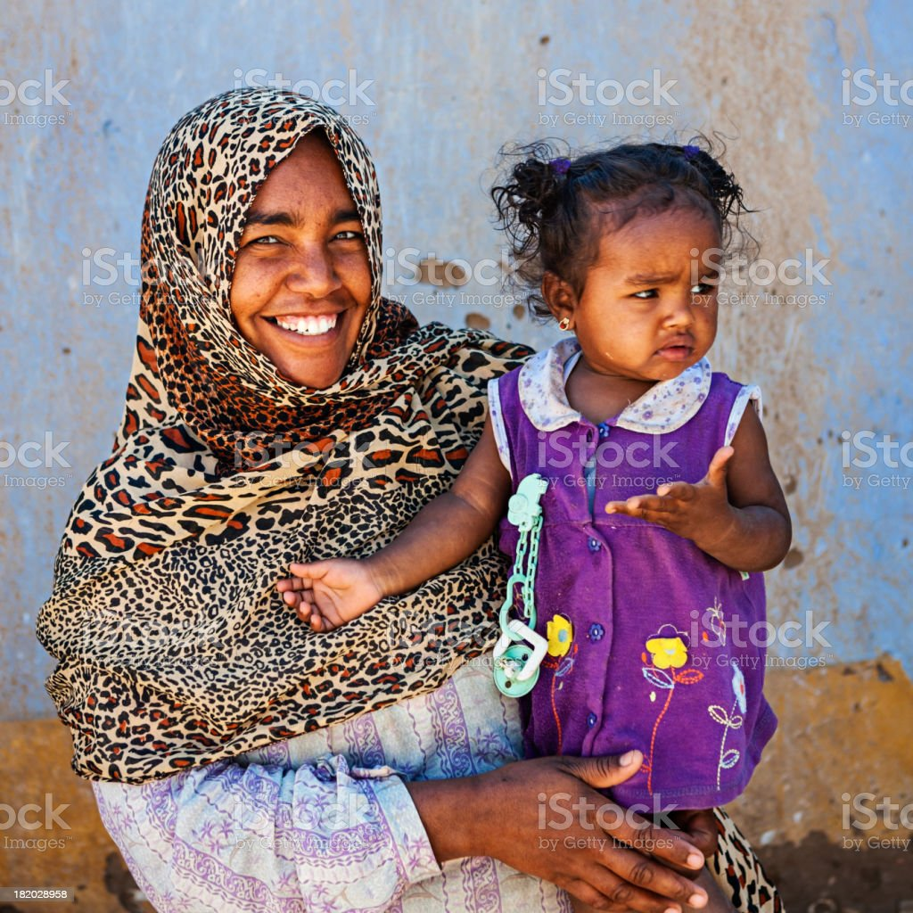 Muslim woman holding her baby, Southern Egypt, Africa stock photo