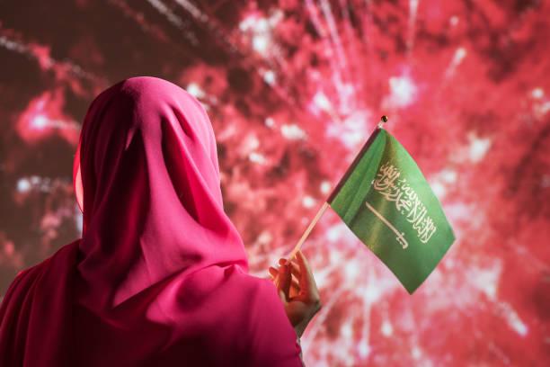 밤에 불꽃 놀이 동안 사우디 아라비아의 국기를 들고 스카프에 무슬림 여성. - saudi national day 뉴스 사진 이미지