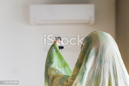 istock Muslim woman in a scarf  holding remote controller from air conditioner inside the room. 1150450289