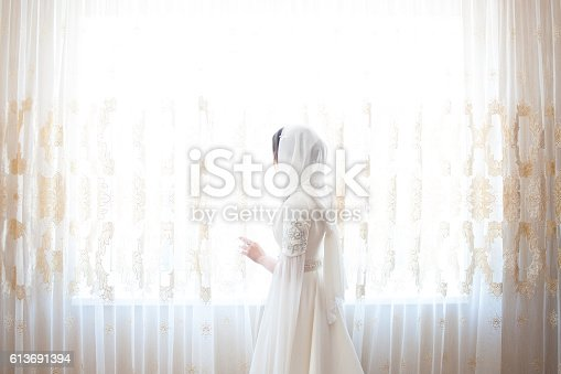 muslim woman in a white headscarf looking out the window