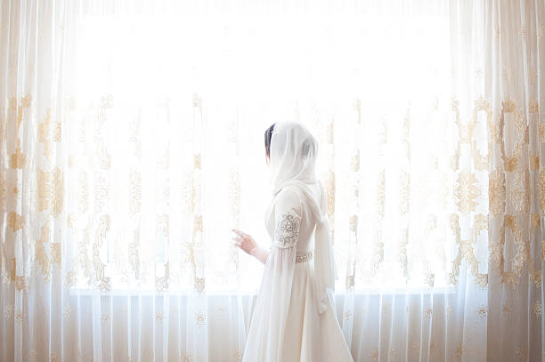 muslim woman in a white headscarf standing at the window - mariage musulman photos et images de collection