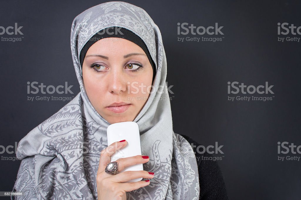 Muslim woman in hijab holding a mobile phone stock photo