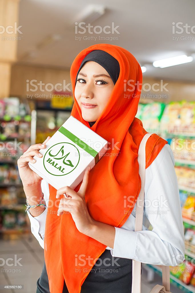 muslim woman in red scarf in supermarket stock photo