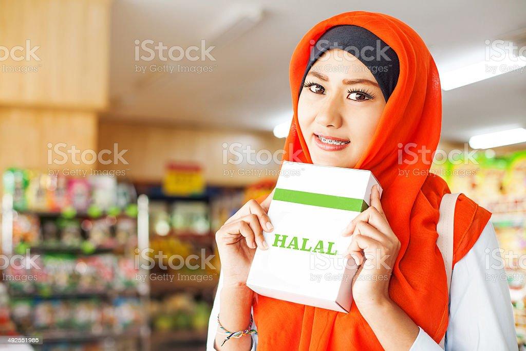 muslim woman in redscarf in supermarket stock photo