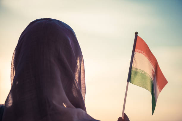 Muslim woman in scarf with Iranian flag at sunset.Concept Muslim woman in scarf with Iranian flag at sunset.Concept iran stock pictures, royalty-free photos & images