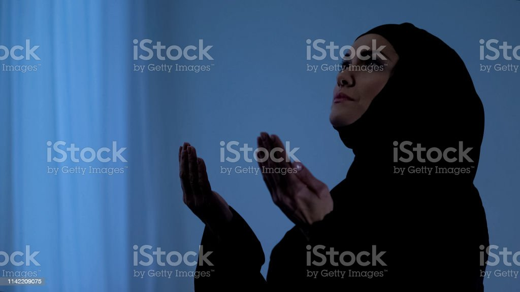 Muslim woman praying with open hands, appealing to sky, god blessing,...