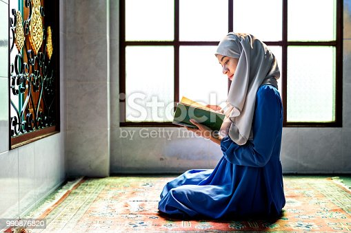 istock Muslim woman reading from the quran 990876820