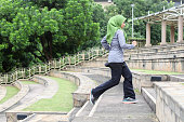 A Malay Muslim woman runner climbing stairs in Malaysia. Wearing a hijab and modest sports clothing doesn't stop them from practising their faith and having an active lifestyle.