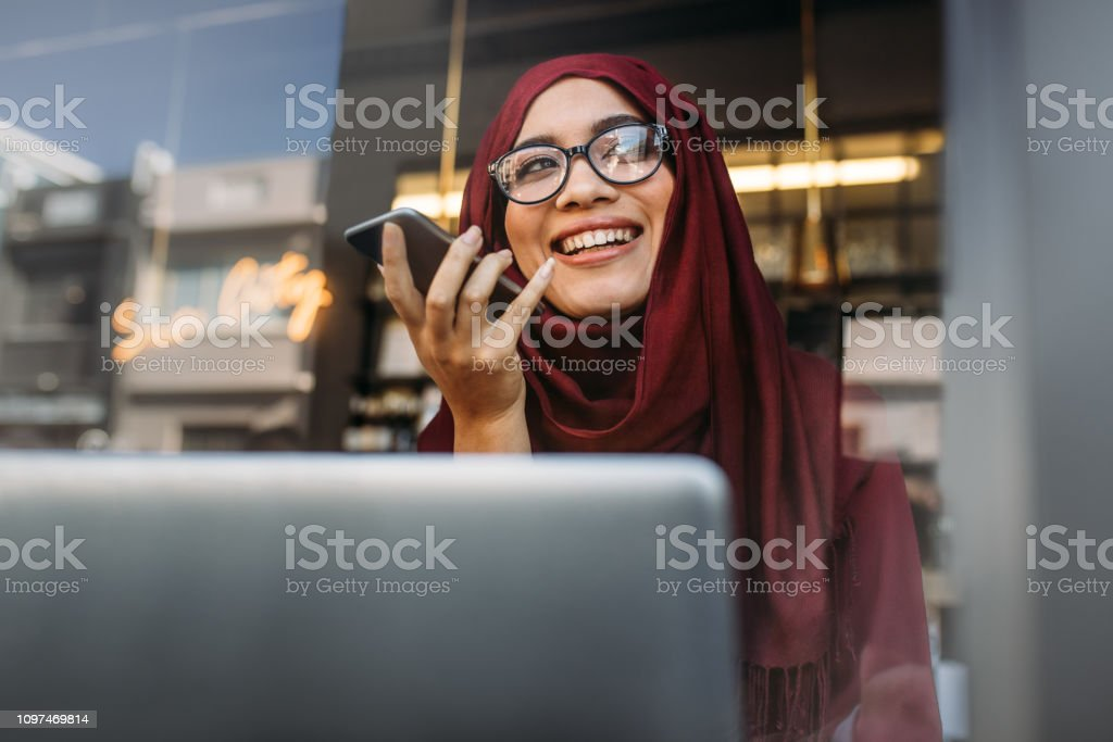 Muslim woman running business online from coffee shop - Foto stock royalty-free di Abbigliamento modesto