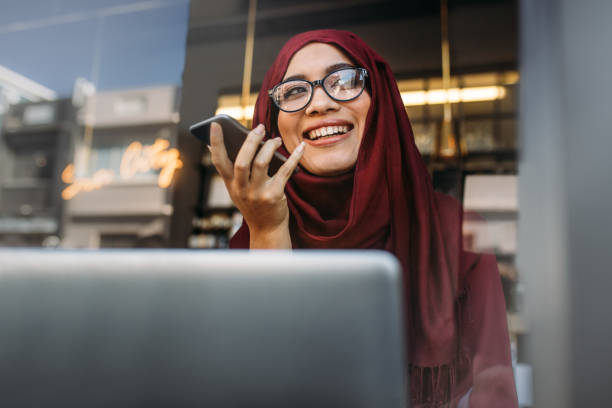 muslim woman running business online from coffee shop - foulard copricapo foto e immagini stock