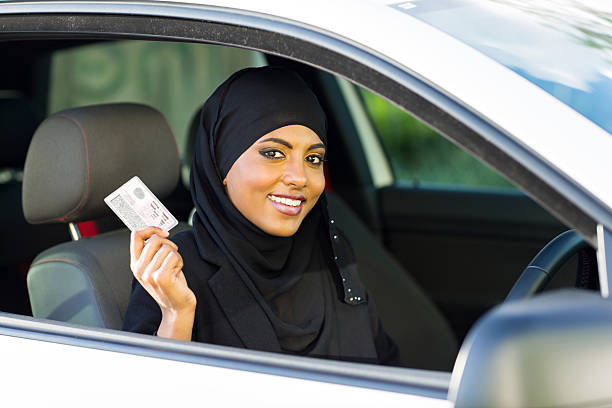 muslim woman showing a driving license stock photo