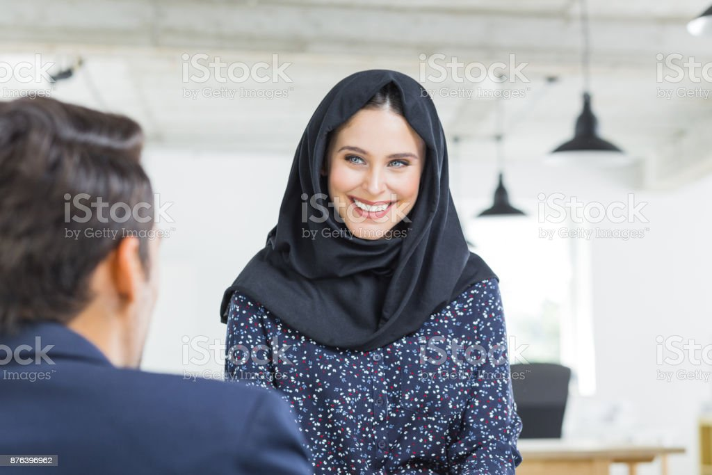 Muslim woman smiling at coworker Smiling young businesswoman in hijab talking with male colleague in office. Muslim woman smiling and looking at coworker. 20-29 Years Stock Photo