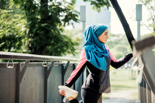 muslim woman stretching after workout at the park - скромная одежда стоковые фото и изображения